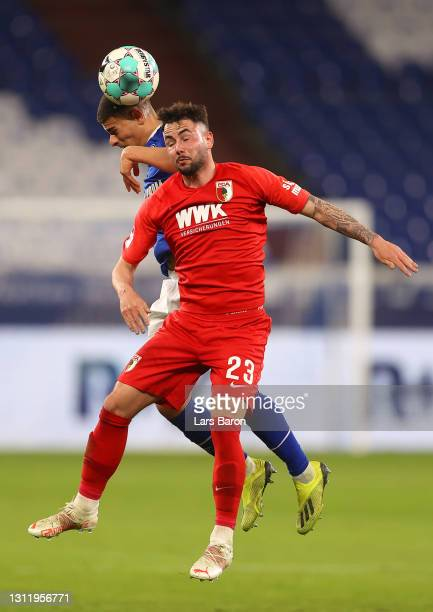 Can Bozdogan of FC Schalke 04 battles for possession with Marco Richter of FC Augsburg during the Bundesliga match between FC Schalke 04 and FC...