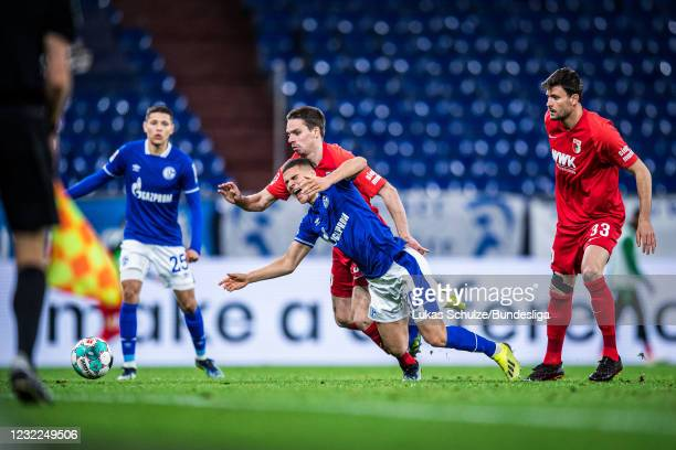 Can Bozdogan of Schalke is fouled by Raphael Framberger of Augsburg during the Bundesliga match between FC Schalke 04 and FC Augsburg at...