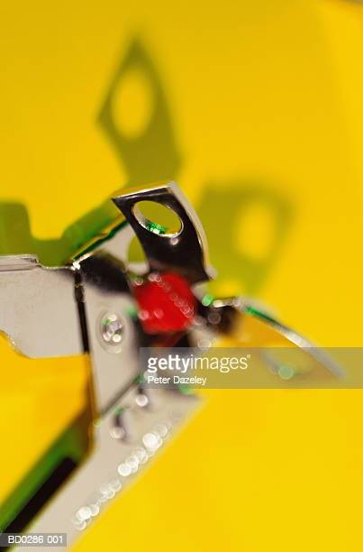 Can opener against yellow background, close-up (brightly lit)