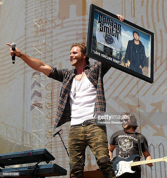 Canaan Smith holds up a plaque for platinum status of his song Love You Like That during a performance during the CMA Fest on the Chevrolet River...