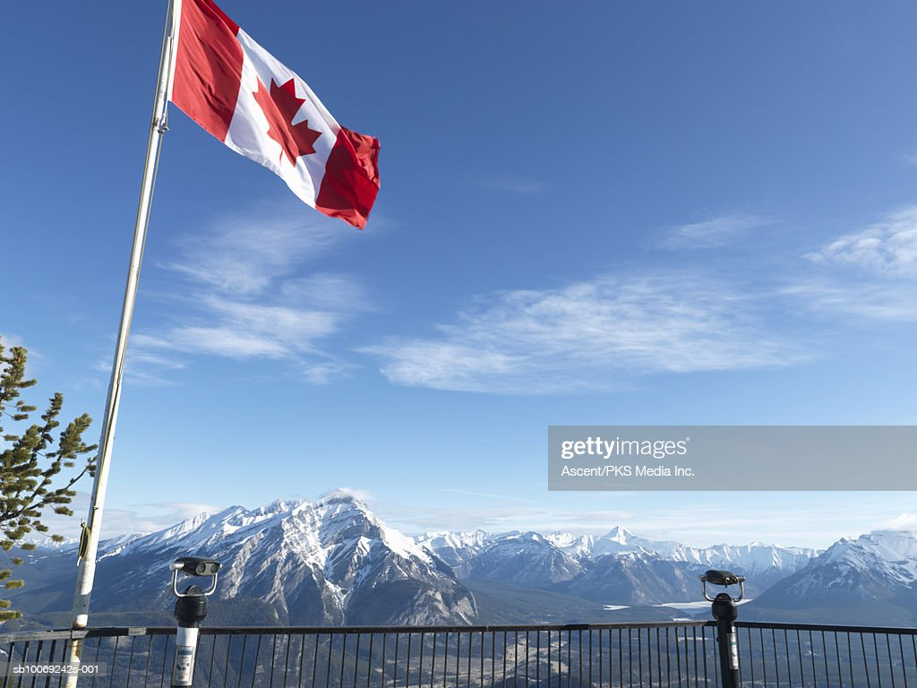 Canada, Alberta, Banff National Park, Canadian flag blowing above viewing deck, mountain range in background : Stockfoto