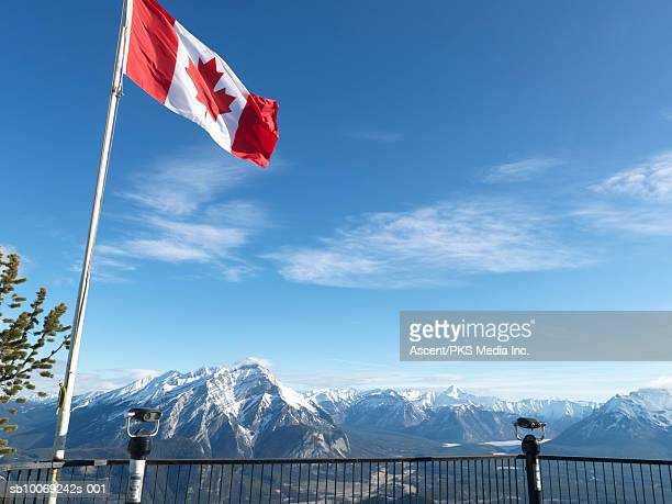 canada, alberta, banff national park, canadian flag blowing above viewing deck, mountain range in background - canadian flag stock pictures, royalty-free photos & images
