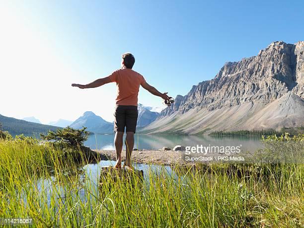 Canada, Alberta, Banff National Park, Man balancing on log in Bow lake