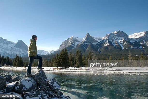 Canada, Alberta, Canmore, woman beside Bow River, side view