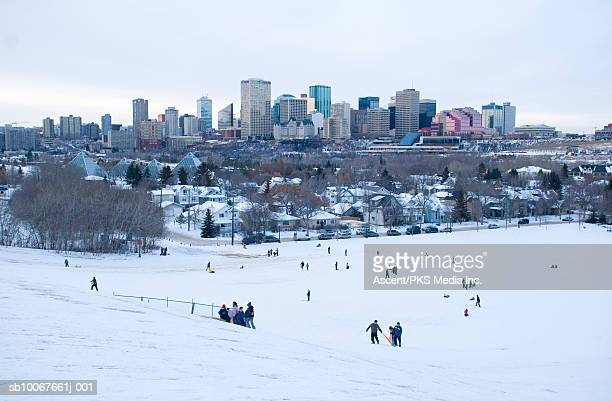 Canada, Alberta, Edmonton, people on Tobaggan hill, with city skyline