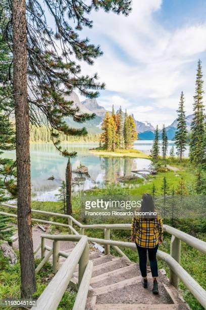 canada, alberta, jasper national park, woman admiring maligne lake and spirit island - montañas rocosas canadienses fotografías e imágenes de stock