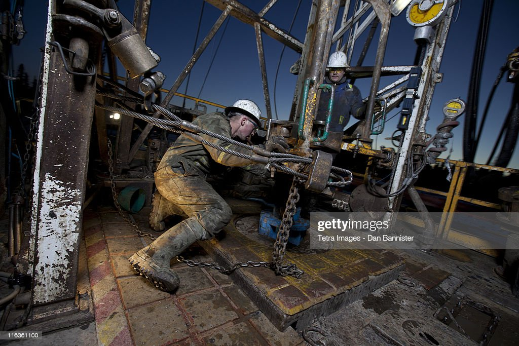Canada, Alberta, Oil workers using oil drill : Stock Photo