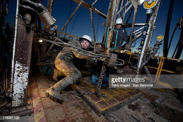 Canada, Alberta, Oil workers using oil drill