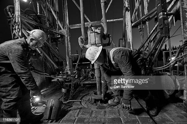 canada, alberta, oil workers using oil drill - oil worker stock pictures, royalty-free photos & images