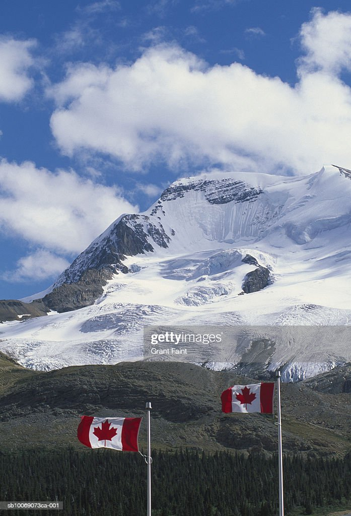 Canada, Banff National Park, Rocky Mountains, Canadian flags with mountains in background : Stockfoto