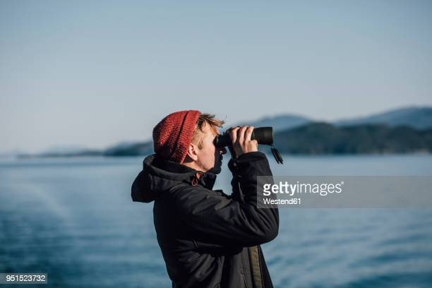 canada, british columbia, man looking through binoculars at the coast - binoculars stock pictures, royalty-free photos & images