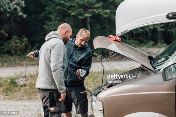 canada, british columbia, two men checking oil level of minivan - oil change stock pictures, royalty-free photos & images