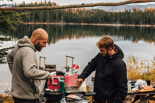 Canada, British Columbia, two men cooking at Blue Lake - gettyimageskorea