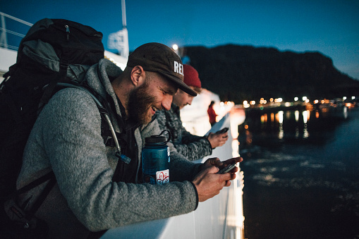 Canada, British Columbia, two men on a boat using cell phones at night - gettyimageskorea