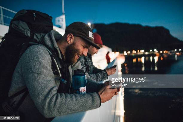 canada, british columbia, two men on a boat using cell phones at night - passagier wasserfahrzeug stock-fotos und bilder