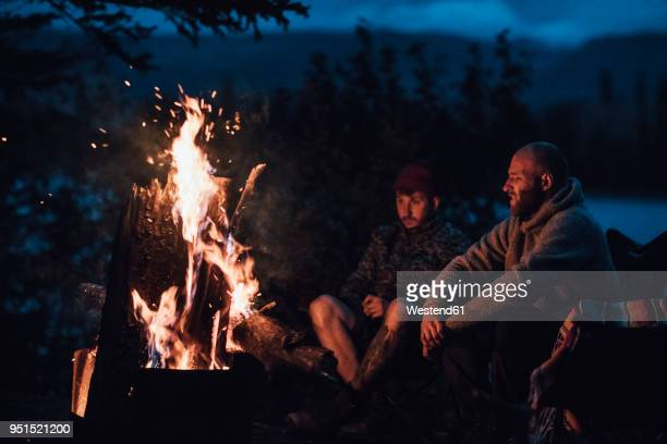 canada, british columbia, two men sitting at camp fire at boya lake at night - lagerfeuer stock-fotos und bilder