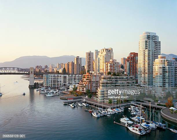 canada, british columbia, vancouver, yachts moored in marina, city skyline in background - vancouver stock pictures, royalty-free photos & images