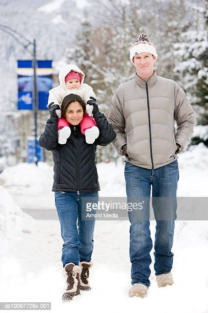 canada, british columbia, whistler, couple walking with baby girl (6-11 months) in snow - 6 11 months stock pictures, royalty-free photos & images