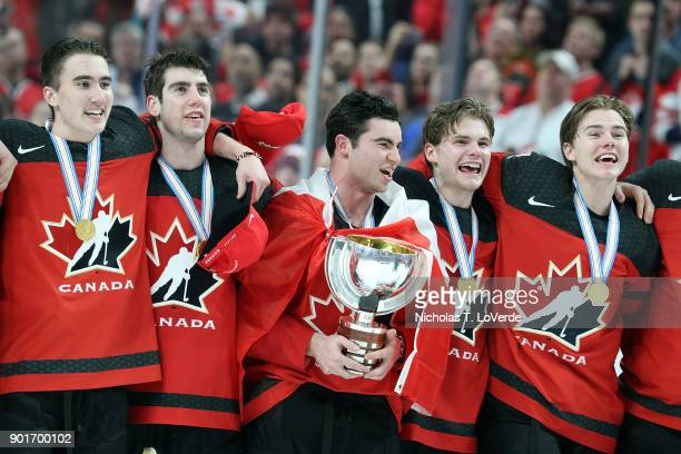 Canada Captain Dillon Dubé holds the Championship trophy and sings the Canadian National Anthem with teammates following their 31 win over Sweden in...