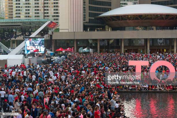 Canada Day 150th Anniversary of confederation Crowd celebrating at Nathan Phillips Square TV screens and Toronto 3D sign