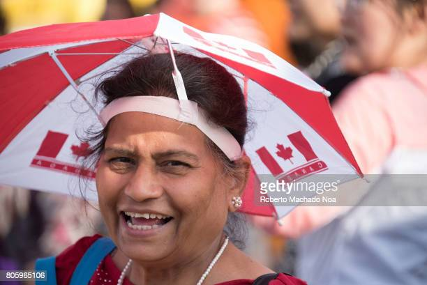Canada Day 150th Anniversary of confederation Female immigrant celebrating and wearing a head umbrella with Canada's colors