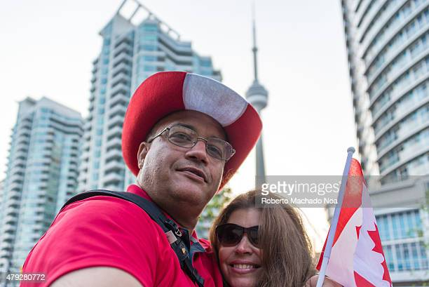 SQUARE TORONTO ONTARIO CANADA Canada Day celebrations in Toronto Immigrants Canadians selfie in the CN Tower wearing the Canadian flag colors
