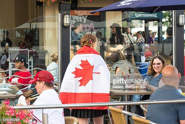 HARBORFRONT TORONTO ONTARIO CANADA Canada Day celebrations in Toronto Restaurant server or waitress with Canadian Flag on the back in Irish Pub Patio...