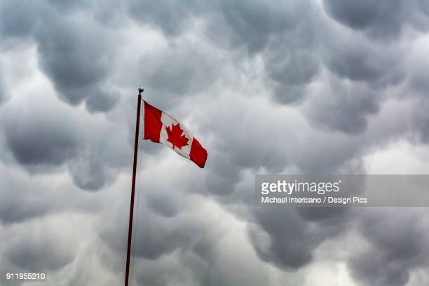 Canada Flag On Pole Against A Dramatic Storm Cloud Formation