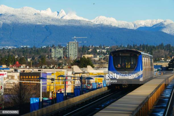 canada line running through richmond and vancouver city with snow capped mountain - vancouver canada stock pictures, royalty-free photos & images