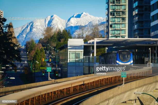 canada line running through richmond and vancouver city with snow capped mountain - richmond british columbia stock photos and pictures