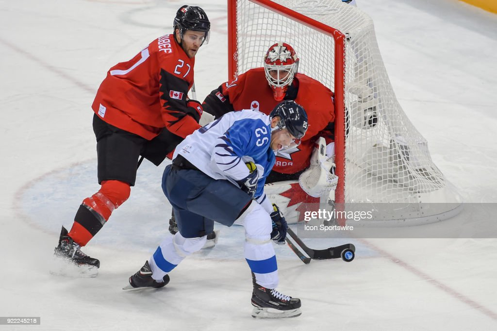 Canada men's hockey defender Cody Goloubef (27) and Finland men's hockey forward Enlund Jonas (25) each fight to get their stick on the puck as Canada men's hockey goalie Kevin Poulin (31) watches during the men's hockey semi final game between Canada and Finland during the 2018 Winter Olympic Games at the Gangneung Hockey Center on February 21, 2018 in PyeongChang, South Korea. Canada advances to the gold medal game with 1-0 victory.