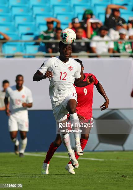 Canada midfielder Alphonso Davies hits the ball with his head during the 1st half of the CONCACAF Gold Cup game with Canada versus Cuba on June 23rd...