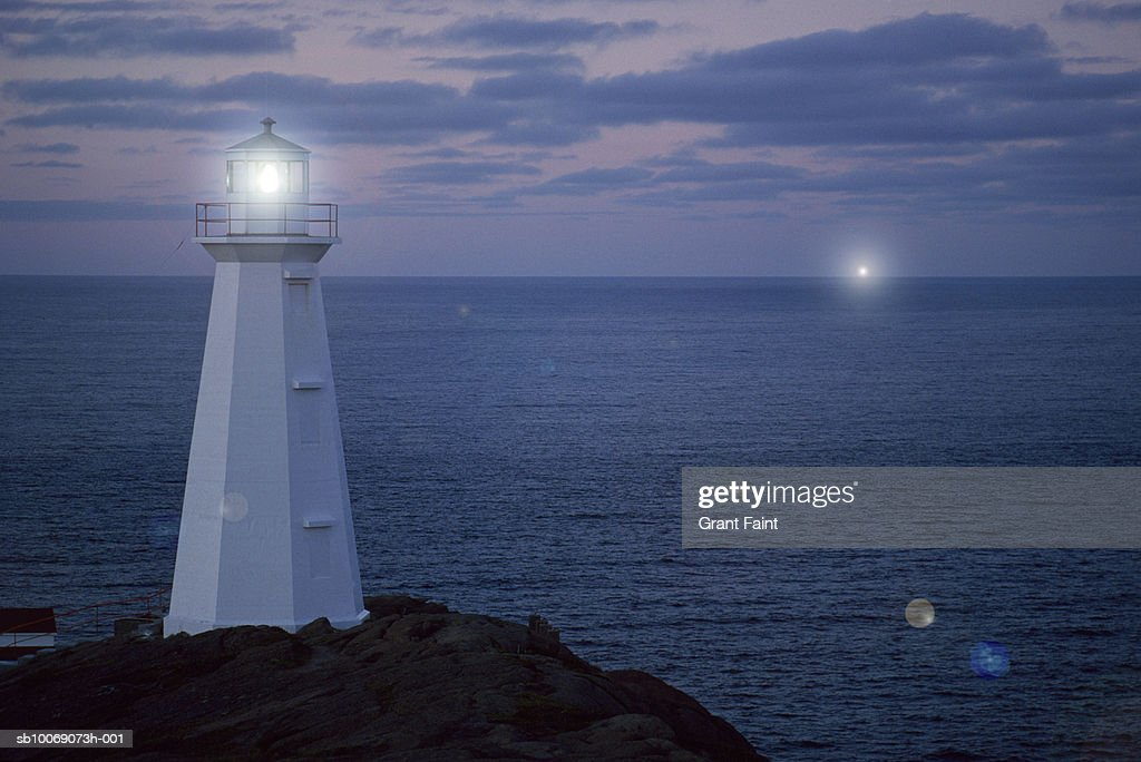 Canada, Newfoundland, illuminated lighthouse on cliff at dusk : Stockfoto