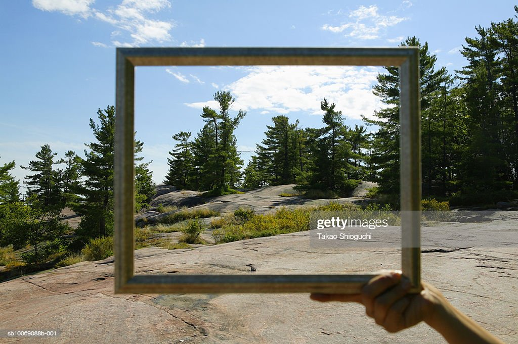 Canada, Ontario, Killbear Provincial Park, Person holding picture frame against trees and cloud : Stockfoto