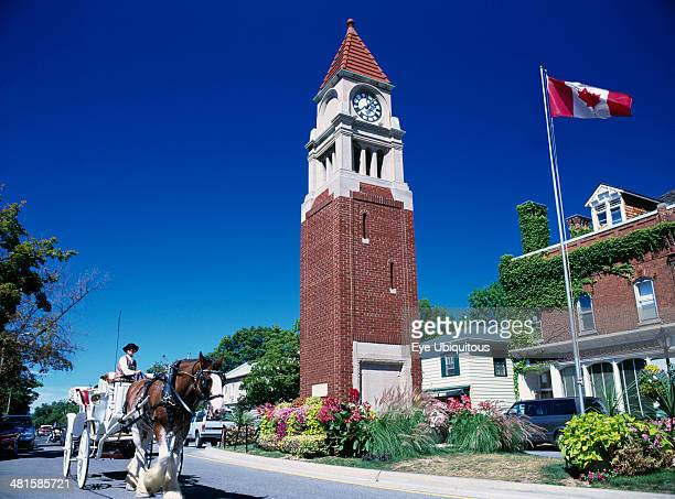 Canada Ontario Niagara on the Lake Queen Street Clock Tower with Canadian flag flying Horse and carriage travelling along road