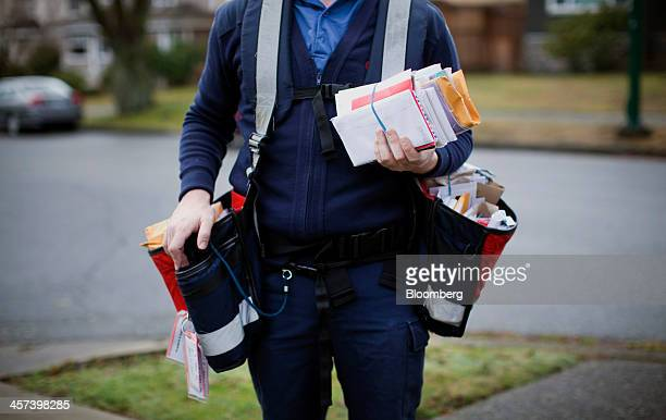 A Canada Post letter carrier looks through a bundle of mail while making deliveries by foot to houses in Vancouver British Columbia Canada on Monday...