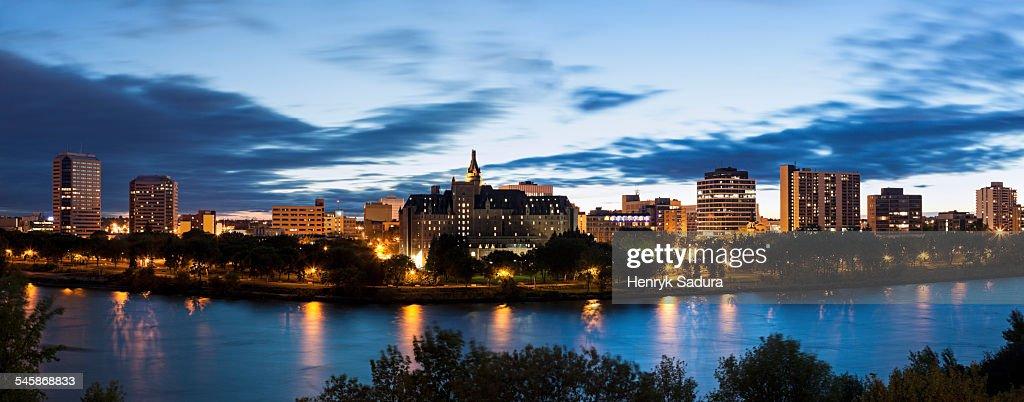 Canada, Saskatchewan, Saskatoon, Panoramic view of city and river at dusk : Stock Photo