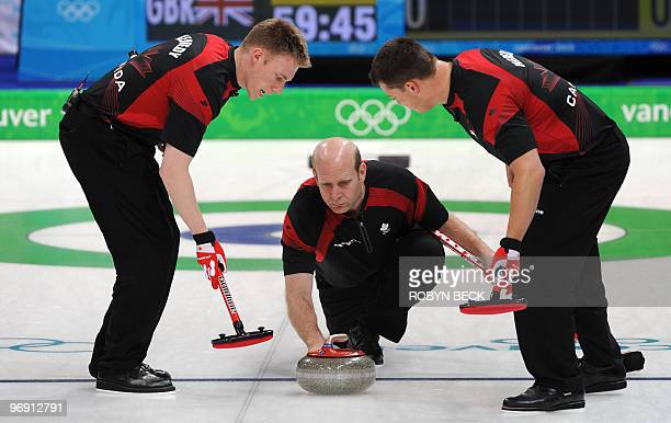 Canada skip Kevin Martin releases a stone as teammates Marc Kennedy and Ben Hebert sweep during the Canada vs Great Britain men's curling round robin...