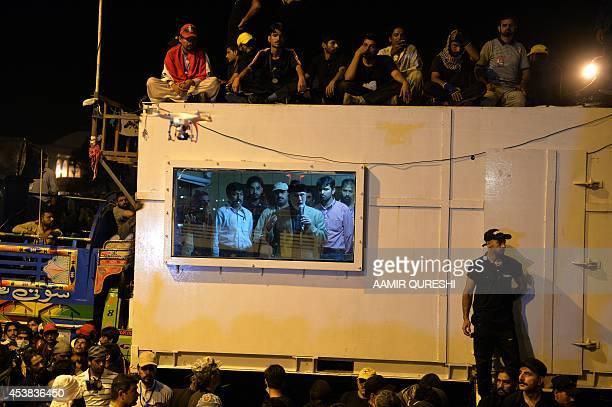 Canadabased preacher TahirulQadri addresses supporters from inside a shipping container in front of the parliament building during the 'Revolution...