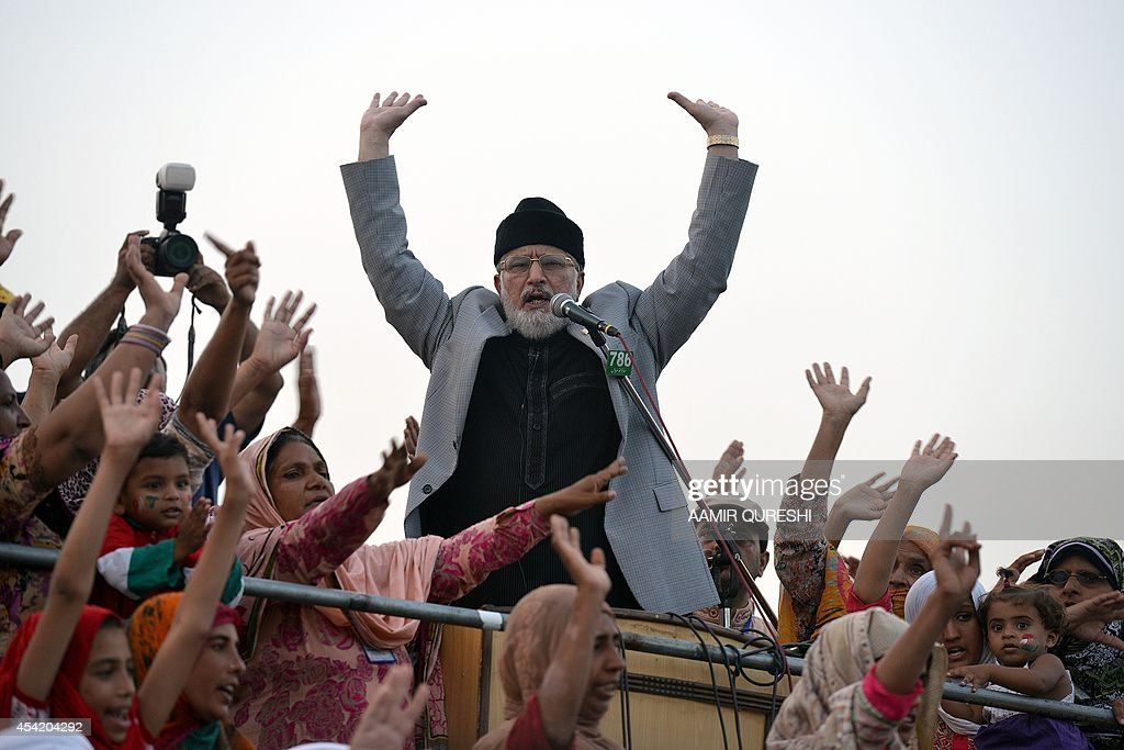 Canada-based preacher Tahir-ul-Qadri gestures as he addresses Pakistani supporters during an anti-government protest in front of the Parliament in Islamabad on August 26, 2014. Pakistani Prime Minister Nawaz Sharif and the country's powerful army chief General Raheel Sharif agreed on August 26 on the need to 'expeditiously' end a political crisis triggered by protests aimed at unseating the government. Thousands of demonstrators led by opposition politician Imran Khan and populist cleric Tahir-ul-Qadri have camped out in the zone since August 15, demanding Sharif resign. AFP PHOTO/ Aamir QURESHI