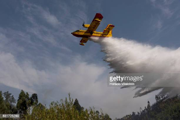 Canadair CL215 firefighting amphibious aircraft drops water over the historical village of Agua Formosa on August 15 2017 in Vila de Rei Portugal...