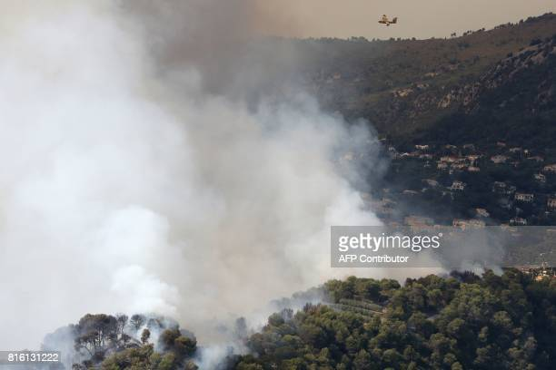 A Canadair waterdropping plane flies over a fire near houses in Castagniers on July 17 2017 / AFP PHOTO / Valery HACHE