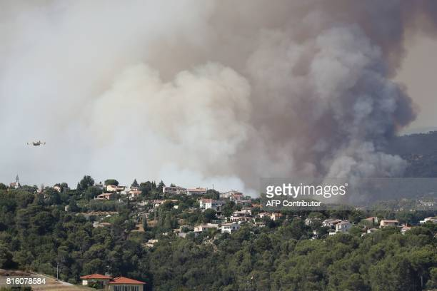 A Canadair waterdropping plane flies over houses during a fire in Castagniers on July 17 2017 / AFP PHOTO / Valery HACHE