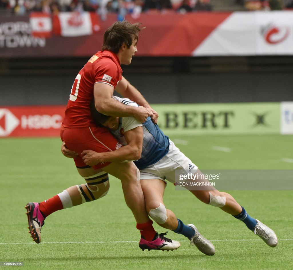 Canada's 7 (red) Pat Kay, is tackled by France 7's Jeremy Aicardi, in HSBC Canada Men's Sevens action at BC Place Stadium in Vancouver, British Columbia on March 11, 2018. Vancouver is the 6th round, played March 10-11, 2018, in the HSBC Men's Sevens 10 round world series. / AFP PHOTO / Don MacKinnon