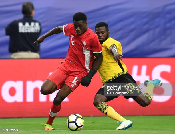 Canada's Alphonso Davies and Jamaica's Kemar Lawrence vie for the ball during their CONCACAF tournament quarterfinal match at the University of...