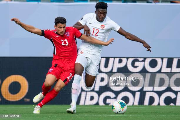 Canada's Alphonso Davies vies for the ball with Cuba's Luis Paradela during their CONCACAF Gold Cup group stage football match at Bank of America...