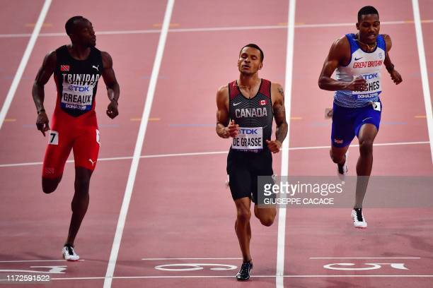 Canada's Andre De Grasse leads Trinidad and Tobago's Kyle Greaux and Britain's Zharnel Hughes in the Men's 200m semifinal at the 2019 IAAF Athletics...