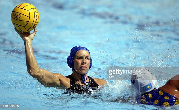 ATHENS GREECE Canada's Ann Dow left passes over the defense of Kazakhstan's Yekaterina Gariyeva in a water polo match during the 2004 Olympic Games...