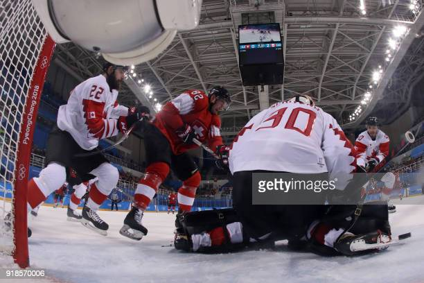 Canada's Ben Scrivens defends his goal against Switzerland's Simon Moser as Canada's Eric O'Dell and Canada's Maxim Lapierre watch in the men's...