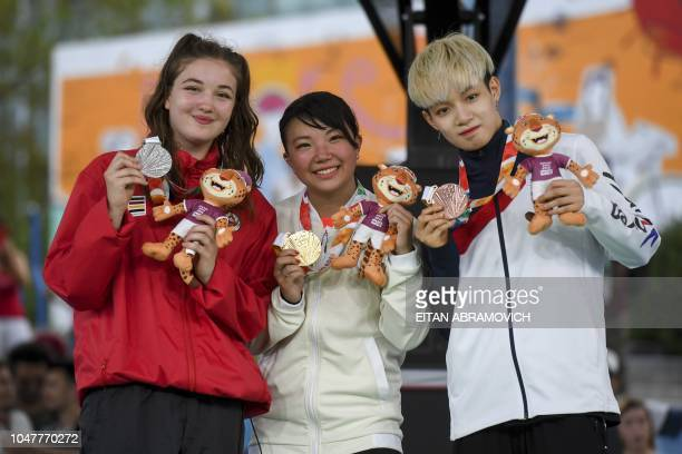 Canada's bgirl silver medal Emma Japan's bgirl gold medal Ram and Korea's bgirl bronze medal Yell pose at the podium at the Youth Olympic Games in...